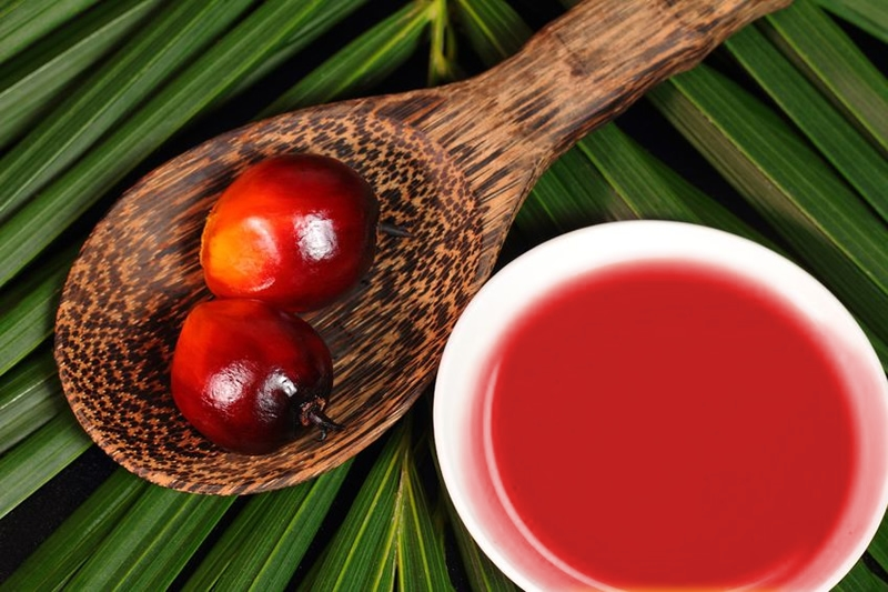 red palm fruit on wooden spoon next to bowl of oil