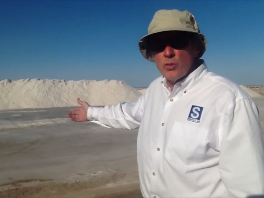 Robert Cain in front of large piles of sea salt