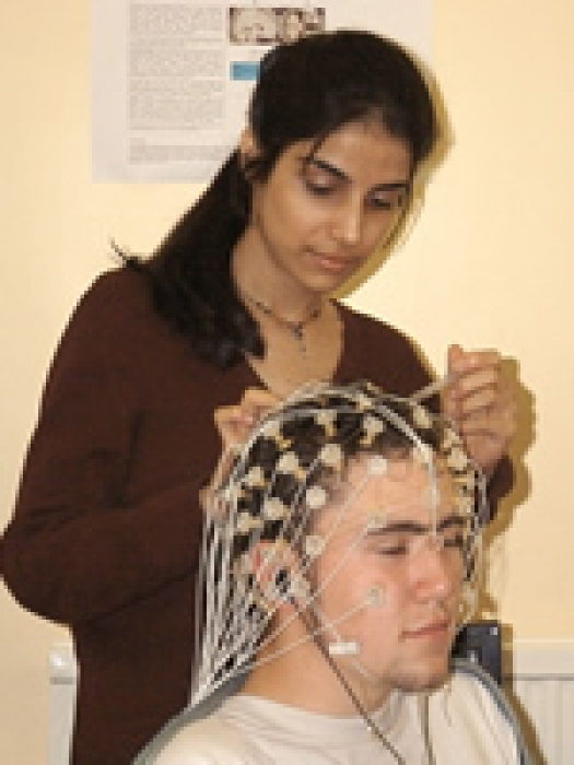 Dr. Aditi Shankardass places electrodes on patient's head.
