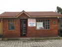 The Guamani Clinic building: small red brick building