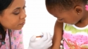 young girl receives a vaccination in her arm