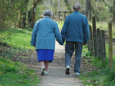 retired couple walking in a park